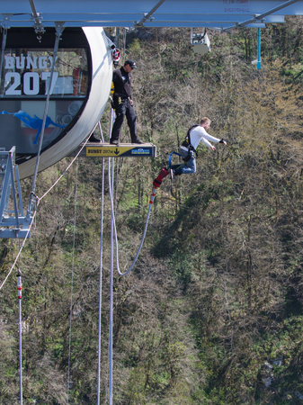 Sochi - April 4, 2017: A brave man with a special rubber rope jumping from the worlds longest pedestrian bridge in the Akhshtyrsky Gorge April 4, 2017, Sochi, Russia