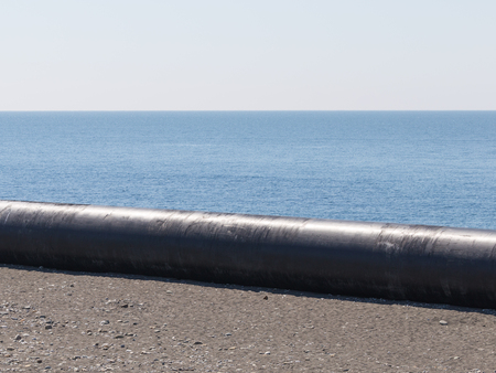 A large metal gas pipe lies near the Black Sea and rocks on the shore