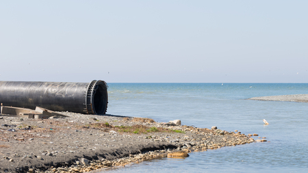 A large metallic gas empty pipe lies near the blue sea and stones on the shore