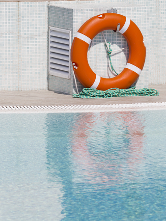 Bright orange lifebuoy by the pool with clear water