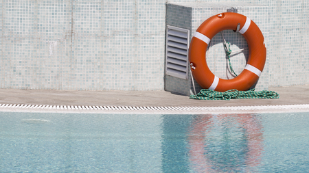 Bright orange lifebuoy by the pool with clear clear water