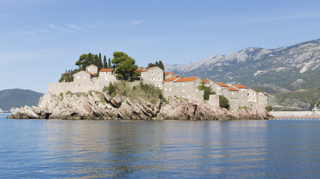elite: Sveti Stefan - September 24, 2017: Beautiful island shine-Stefan view from the Adriatic Sea, and reflections in the water in the morning September 24, 2017, Sveti Stefan, Montenegro
