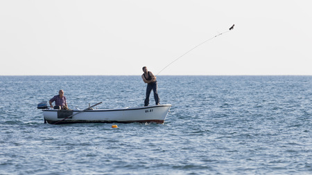 Ulcinj riviera - October 1, 2017: Two fishermen chase fish on the net with cargo on a rope, from a boat in the blue sea on the Great Montenegrin beach, Ulcinj Riviera, Montenegro Editorial