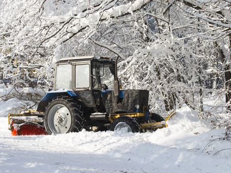 Tractor, with large wheels, to clean snow with a brush and scraper stands outside cold winter and white snow around Stock Photo
