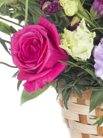 beautiful bright crimson rose in a floral bouquet in a basket on a white isolated background Stock Photo