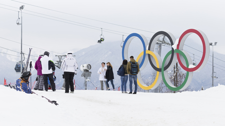 Sochi - March 29, 2017: Men and women photographed near the Olympic rings in the Olympic ski cluster March 29, 2017, Sochi, Russia Redactioneel
