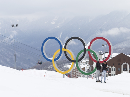 Sochi - March 29, 2017: A man and a woman make a selfie near the Olympic rings in the Olympic ski cluster March 29, 2017, Sochi, Russia Editöryel