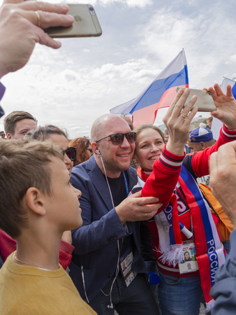 Moscow - June 14, 2018: Happy Russian football fans at the World Cup in Moscow are photographed with TV host Anatoly Kuzevich. June 14, 2018, Moscow, Russia Editöryel
