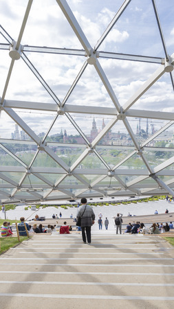 Moscow - June 14, 2018: People walk in a modern beautiful park Charge and a glass dome near, through which the Kremlin is visible, vertically June 2018, Moscow, Russia