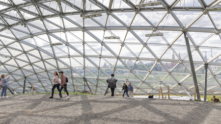 Moscow - June 14, 2018: People walk in a modern beautiful park Charge and a glass dome near, through which the Kremlin is visible June 2018, Moscow, Russia