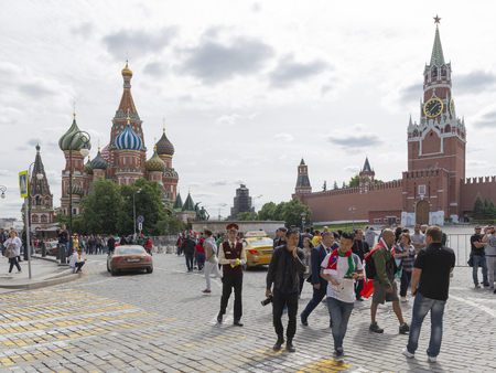 Moscow - June 14, 2018: many happy people and tourists are walking around the St. Basils Cathedral during the World Cup and the Spasskaya Tower of the Kremlin with a clock June 14, 2018, Moscow, Russia