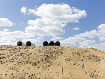 a large mountain of yellow sand and empty large pipes from above and a bright blue sky with clouds