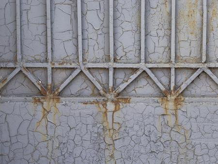 gray old painted cracked metal fence with vertical stripes and cracks and the paint peeling off and showing rust with smudges