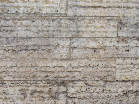old wall of gray natural stone with sags and potholes, laid like a brick and thin seams between a stone