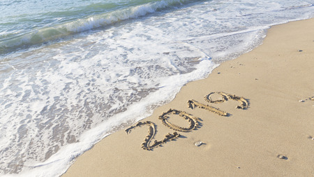 Figures of the new year 2019 are written on the clean yellow sand on the beach and the sea waves with foam roll ashore