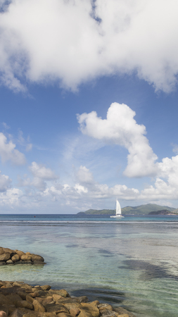 Beautiful seascape with a white yacht with a sail and green mountains, Seychelles