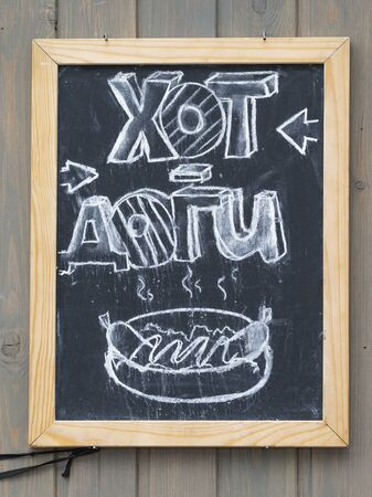 inscription in white chalk hot dogs in Russian and drawing on a black slate and an arrow