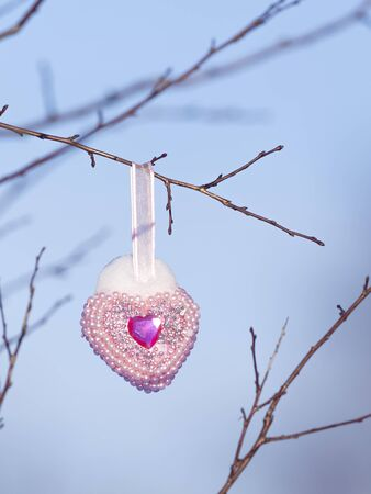 Christmas toy in the form of a pink-purple heart with pearls hanging on a bare tree branch and snow on it against a blue sky