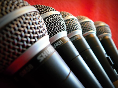 several Shure microphones sm58 on a red background