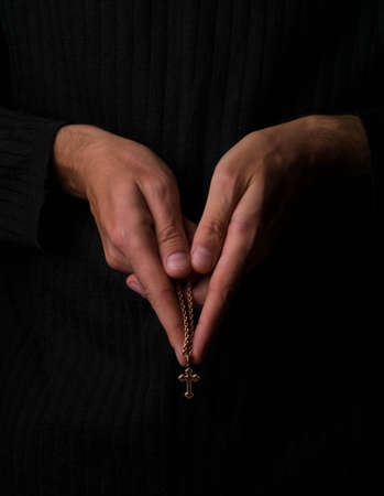 Prayer with a cross in his hands on a black photo