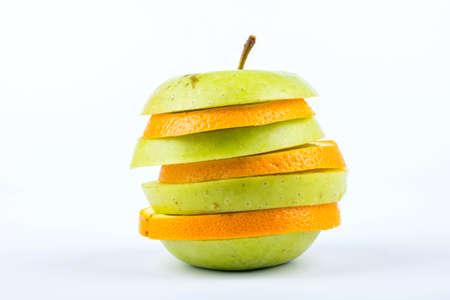 manzana: Apple y rodajas de naranja apilados en una pieza de fruta en un blanco Foto de archivo
