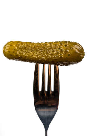Small pickled cucumber on a fork on a white background photo