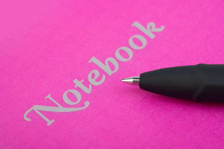 A pen rests on a closed pink notebook photo