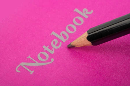 Pencil emphasizes the inscription on the closed notebook pink Stock Photo