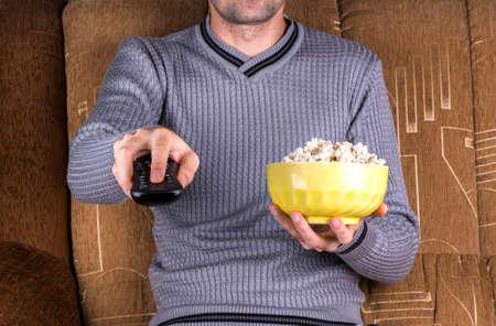 남자가 리모컨의 채널을 전환하고 TV가 손에 들고있다.