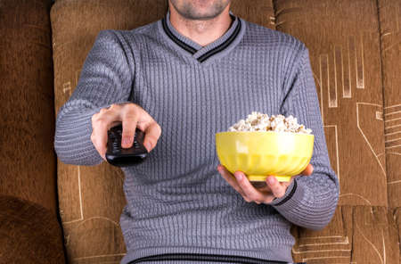 Man switch channels on the remote control and tv holds in his hand popkor