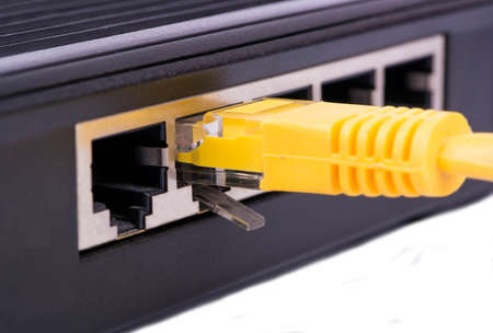 rj45: Yellow rj45 lan cable is connected to the modem port Stock Photo