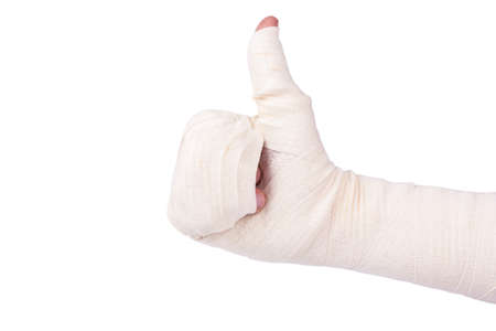 Damaged bandaged the mans hand with a raised thumb on a white background