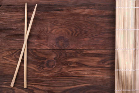 white fish: Chopsticks and folded bamboo napkin on a wooden background Stock Photo