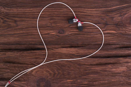Heart of white headphones on a brown wooden background symbolizing love