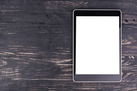 Tablet PC with a blank screen is a dark wooden background