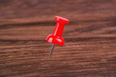 red pushpin: Red pushpin on a brown wooden background Stock Photo