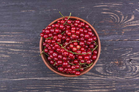 not full: Full bowl of fresh redcurrant not dark wooden background top view