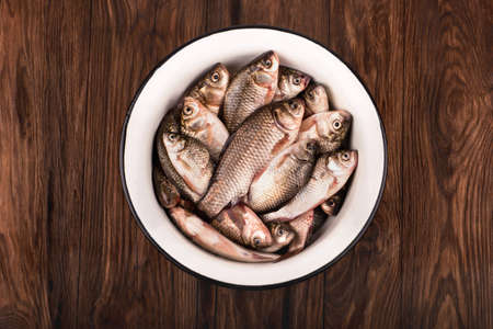 crucian: Catch of fishing. Full bowl of crucian carp on a brown wooden background Stock Photo