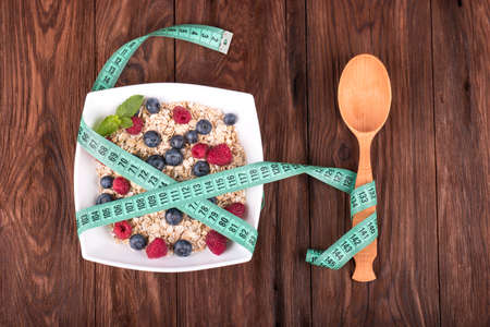 to the diet: Symbol of diet, oatmeal with raspberries, blueberries and spoon wrapped meter on a wooden background Stock Photo