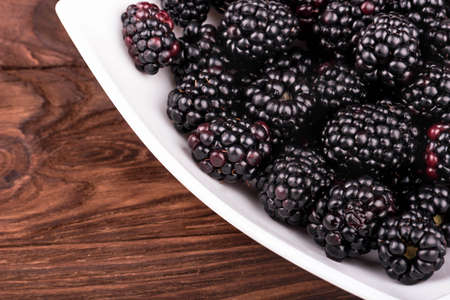 brambleberry: Part of a white bowl with blackberries close-up on wooden background Stock Photo