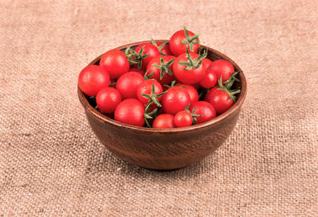 sacking: Full bowl of fresh red cherry tomatoes on sacking