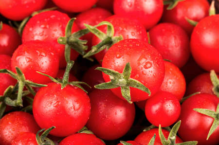 Fresh small red cherry tomatoes with drops close-up Banque d'images