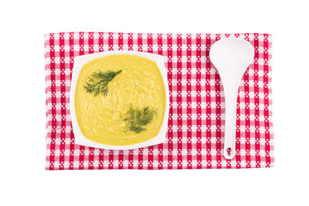 plastic scoop: Cream soup of different vegetables on a plate with a plastic scoop on a towel