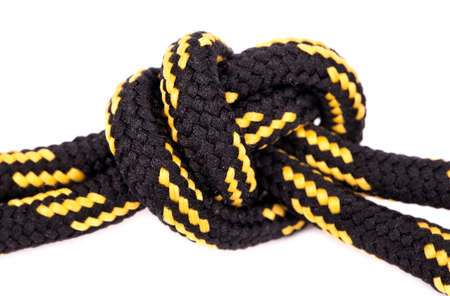 tied in: Black and yellow shoelaces tied in a knot on a white background closeup