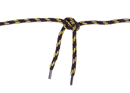 tied in: Black and yellow shoelaces tied in a knot on a white background Stock Photo