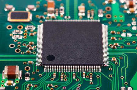 electrical parts: The green microcircuit chip closeup Stock Photo