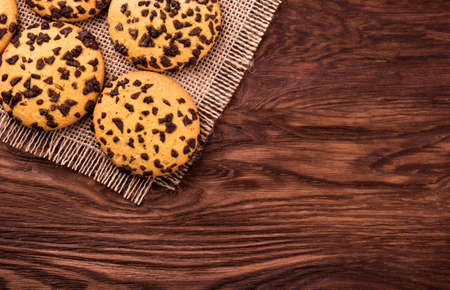 palatable: Several cookies with chocolate on sacking and an empty wooden background top view Stock Photo