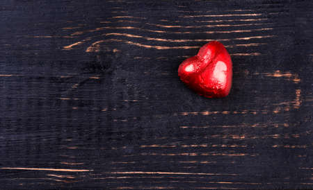 lonely heart: Lonely heart chocolate in a foil on an empty dark wooden background