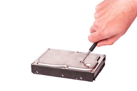 disassemble: Mans hand with a screwdriver repair hard drive (HDD) Stock Photo