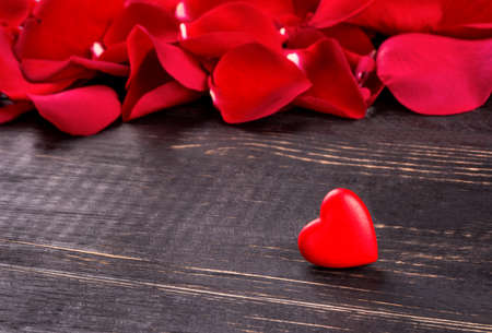 lonely heart: Lonely heart on the background of scattered red rose petals
